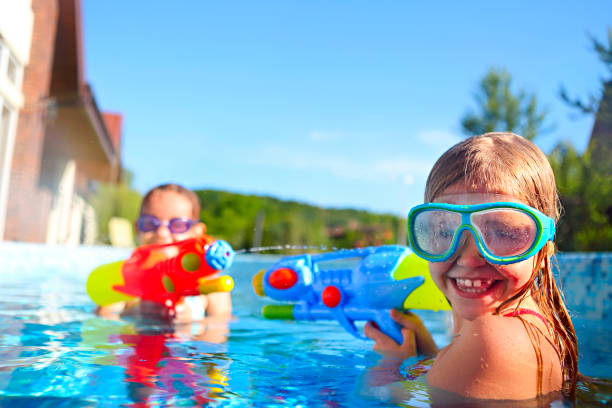 Funny little girls playing with water guns in the pool stock photo