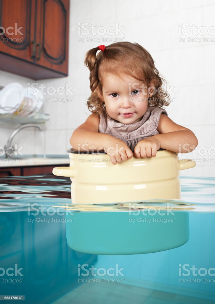 Funny little kid swim in pan in the flooded kitchen, rowdy creative concept stock photo