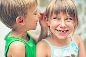 Little boy whispering to his sister's ear.