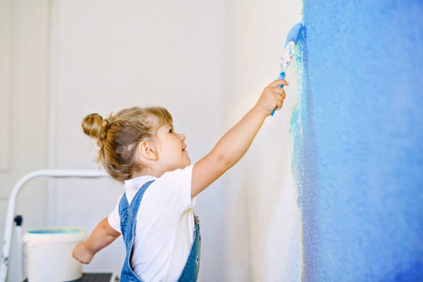 Funny little toddler girl painting the wall with color in new house. Family repair apartment home. Happy baby child paints the wall, choosing color with palette, having fun with brush, indoors stock photo