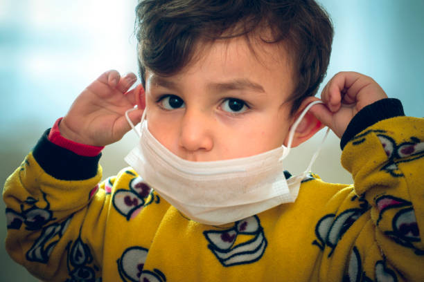 Funny looking 3 years old curious baby in pajamas trying to wear surgical mask stock photo