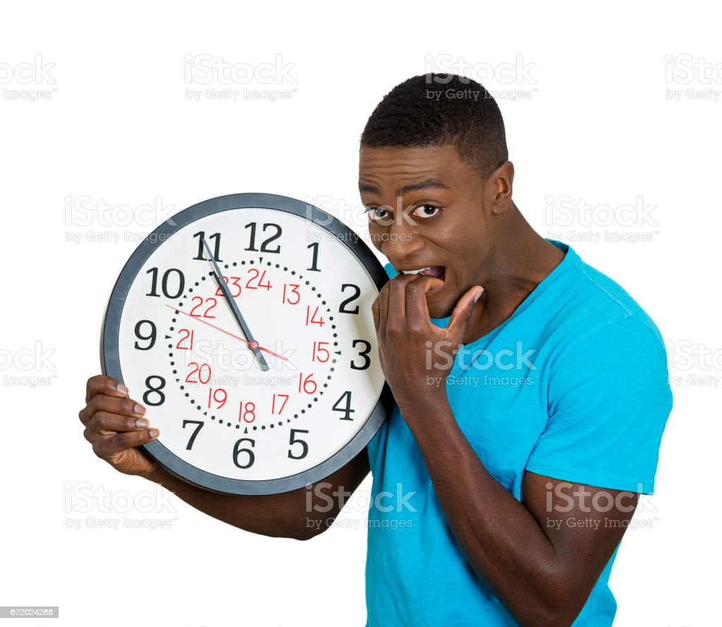 funny looking man student holding wall clock, stressed biting fingernails pressured by lack, running out of time, stock photo