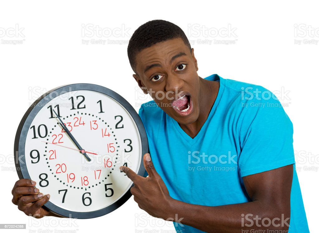 funny looking man student holding wall clock, stressed biting fingernails pressured by lack, running out of time, late meeting, interview, appointmen stock photo