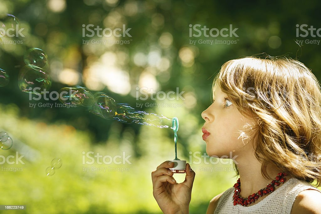 Funny lovely girl blowing soap bubbles royalty-free stock photo