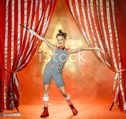 Beautiful young girl dressed in a magician costume shows the circus performance. The preadolescent girl is smiling looking at the camera. She is waving her arms wide apart. The girl holding the magic wand in the hand. Studio shooting red background with glowing star and the striped theatrical curtain