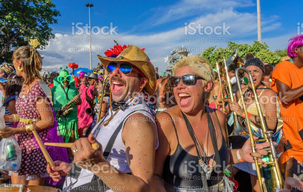 Funny man and woman of Bloco Orquestra Voadora playing drum and trombone, singing and dancing on the background of other musicians stock photo