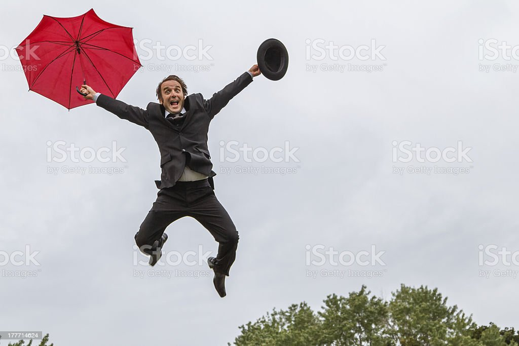Funny Man Falling From Sky with Red Umbrella stock photo