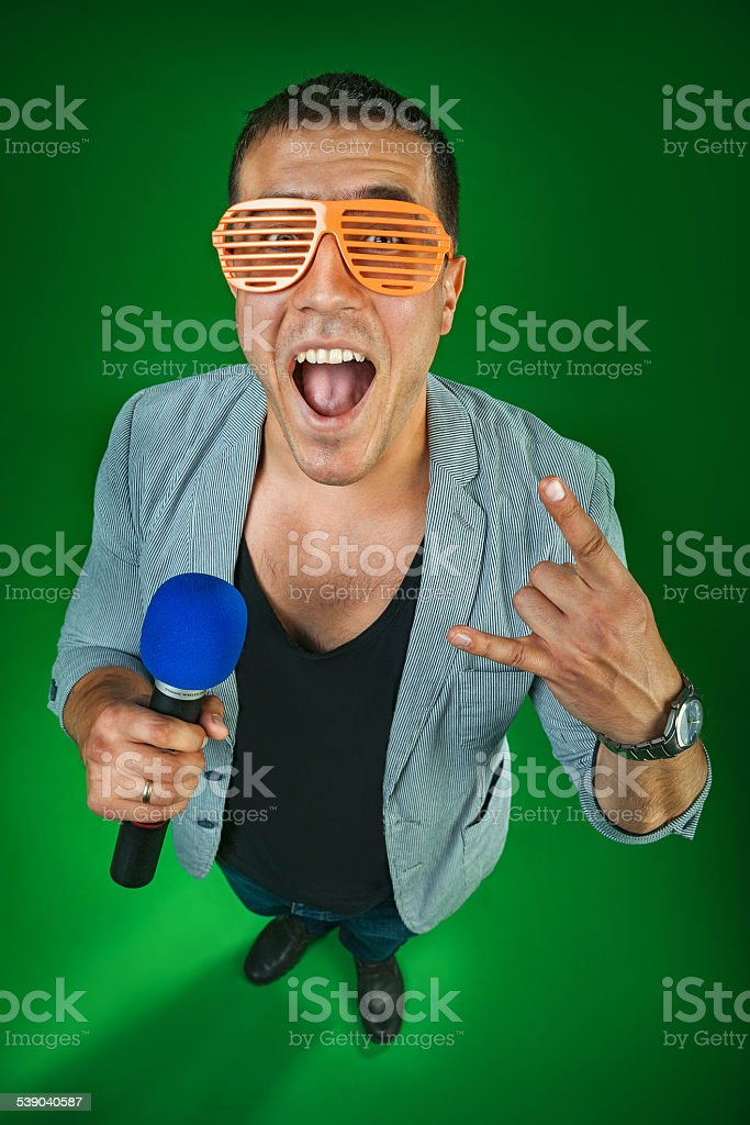 funny man in glasses,green background,blue microphone stock photo