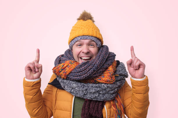 Funny man in several hats and scarfs pointing with index finger up Handsome caucasian funny man in several hats and scarfs pointing with index finger up on pink background. Winter fashion. warm clothing stock pictures, royalty-free photos & images