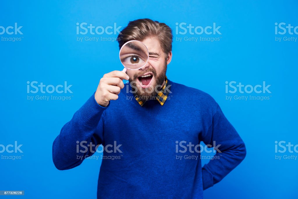 Funny man watching his eyeball in the magnifying glass stock photo