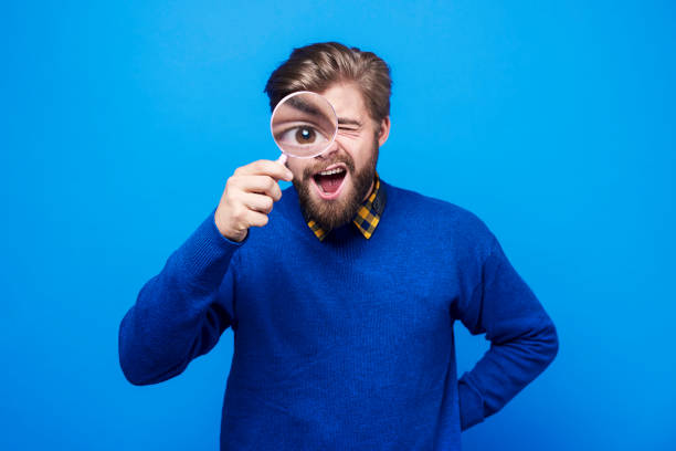 Funny man watching his eyeball in the magnifying glass Funny man watching his eyeball in the magnifying glass magnifying glass stock pictures, royalty-free photos & images