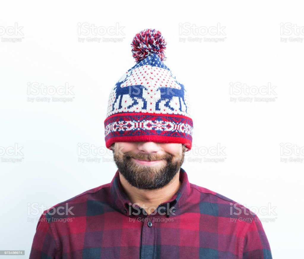 Funny man wearing a winter cap Close up of funny man wearing a winter cap covering his eyes on white background Adult Stock Photo