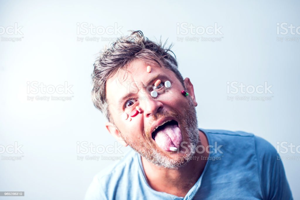 Funny man with a lot of different pills on his face. Medicine concept royalty-free stock photo