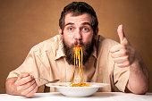 funny man with beard eating noodles showing thumb up - looking at camera