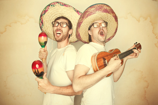 Two men sing happily and enthusiastically with goofy expressions on their face, glasses, and big sombreros, both playing instruments (maracas and ukelele).  Aged yellow paper background to give a rustic feel.  Horizontal.