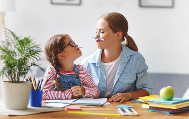 lustige Mutter und Kind Tochter Hausaufgaben schreiben und lesen zu tun – Foto