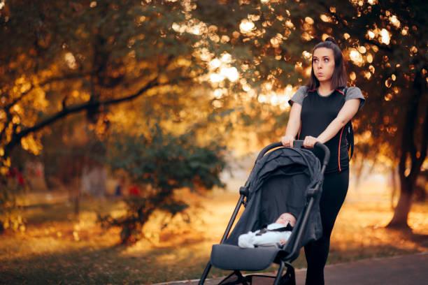 Lustige Mutter trägt sportliche Outfit Pushing Kinderwagen im Park – Foto