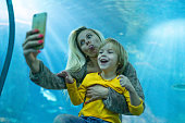 Young mother is taking funny selfie with son in public aquarium
