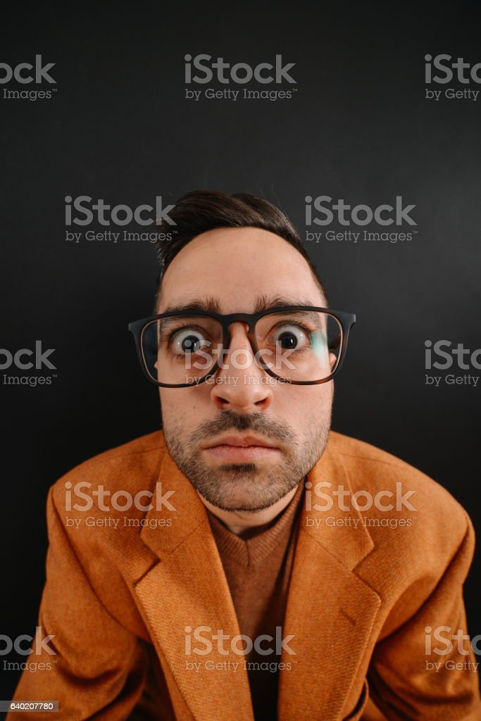 Funny nerd with geek glasses making facial expression stock photo