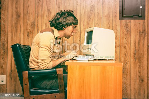 Goofy 1980s Computer Worker looking intently at a vintage computer screen.  Retro colored and styled image with wood panelling in the background.