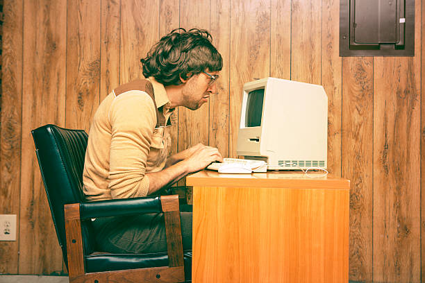 funny nerdy man looking intensely at vintage computer - desktop foto stock-fotos und bilder