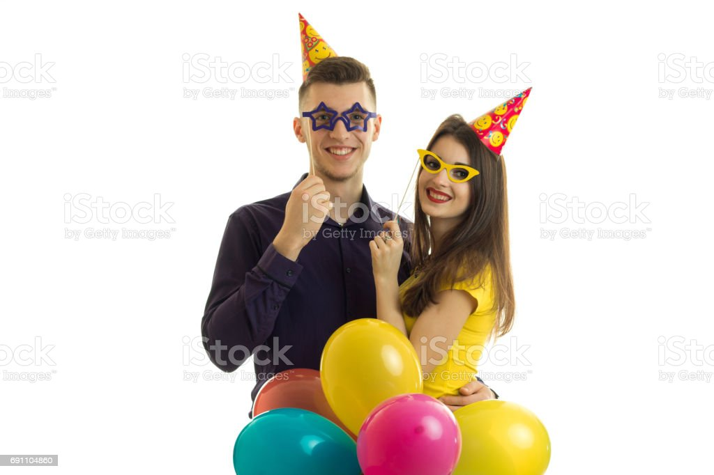 funny nice guy and girl holding paper glasses a lot of colored balloons and smiling stock photo