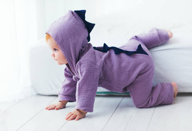 funny, nine month old, infant baby girl in dinosaur costume, going down from the bed stock photo