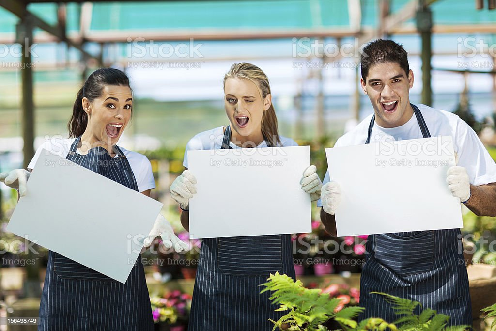 funny nursery workers with white board royalty-free stock photo