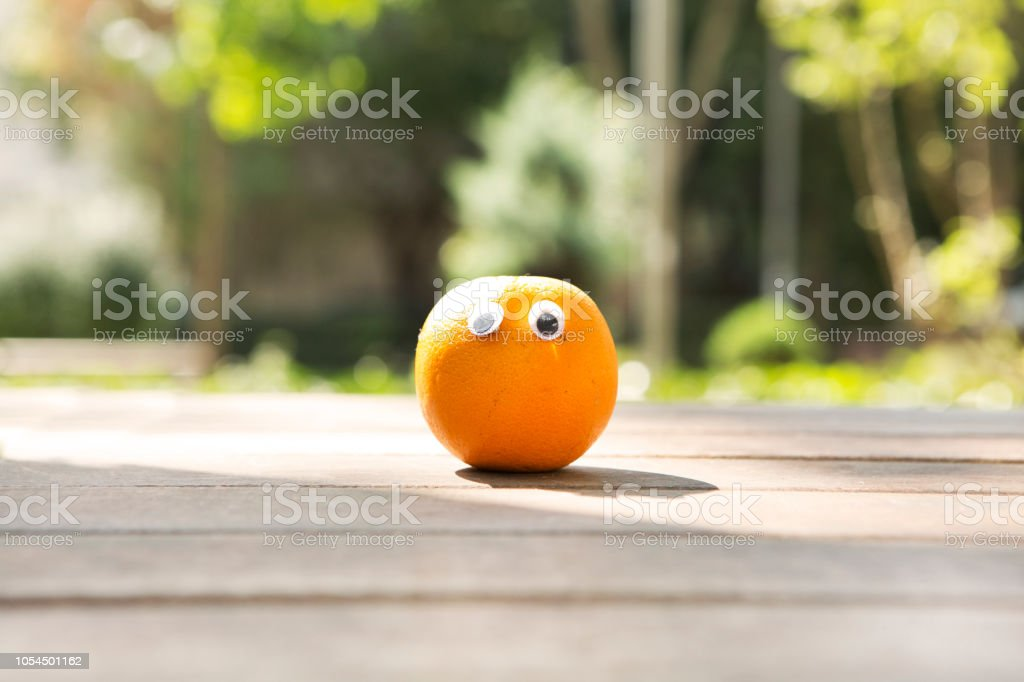 Funny fruit and vegetables with eyes on wooden table in public...