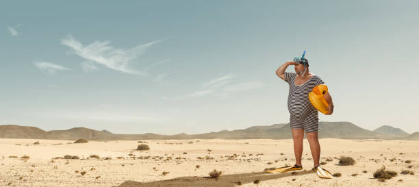 Funny overweight swimmer searching for the beach  in the middle of the desert stock photo