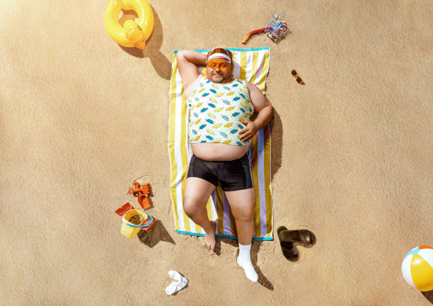 Funny overweight tourist getting tanned on the beach stock photo