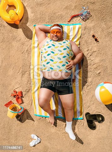 High angle view of funny overweight tourist resting on the beach