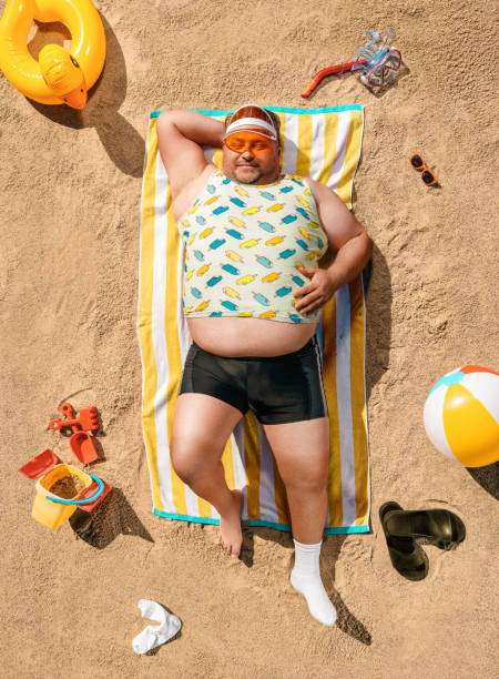 Funny overweight tourist resting on the beach stock photo