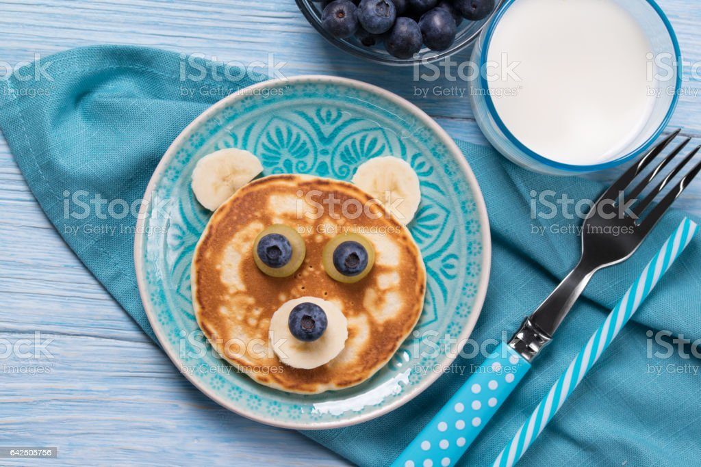 Funny pancake in a shape of teddy bear, food for kids idea, top view stock photo