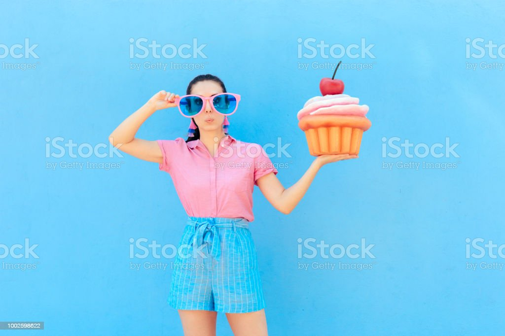 Funny Party Girl with Big Sunglasses and Huge Cupcake stock photo