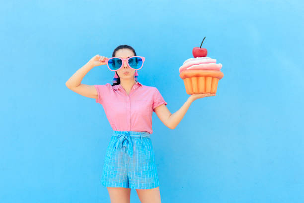 funny party girl with big sunglasses and huge cupcake - big cake stock photos and pictures