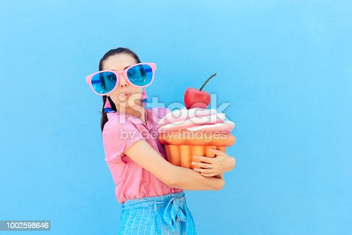Humorous woman wearing silly glasses holding huge cake