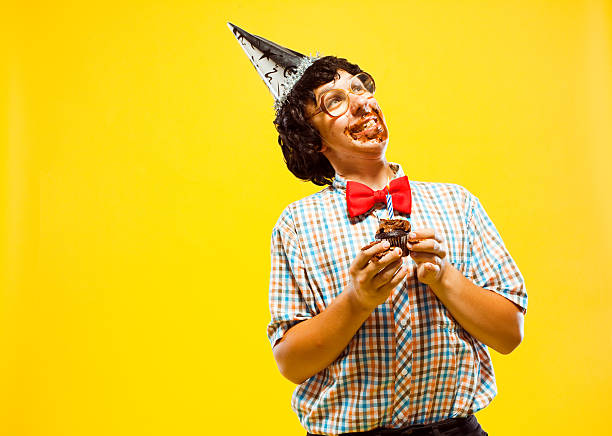 funny party nerd teen boy holding cupcake frosting facial disaster - nerd boy eating stock photos and pictures