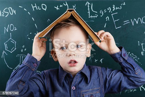 istock Funny portrait clever pupil boy on school board background 578267240