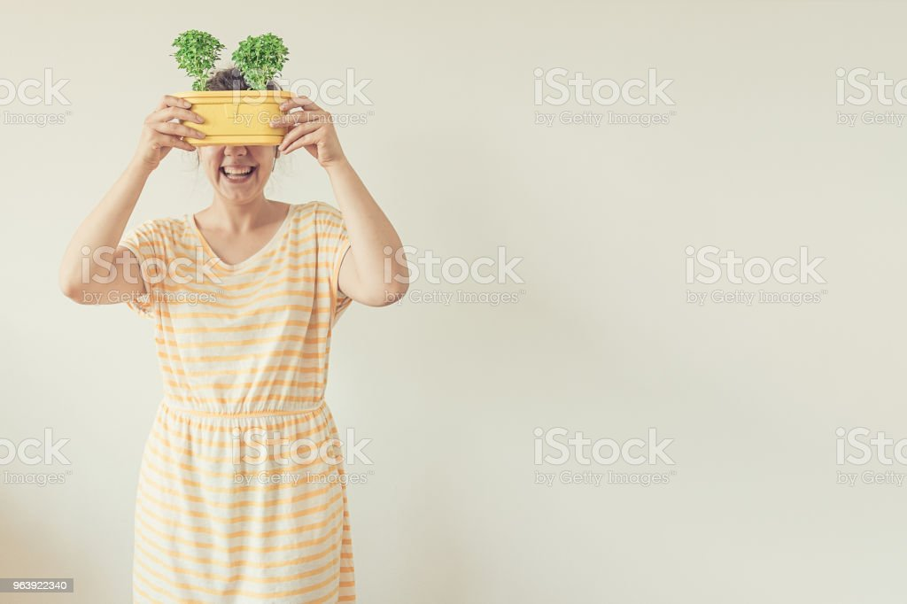 Funny portrait girl holding plants in front of her face after successful re-potting - Royalty-free Adult Stock Photo