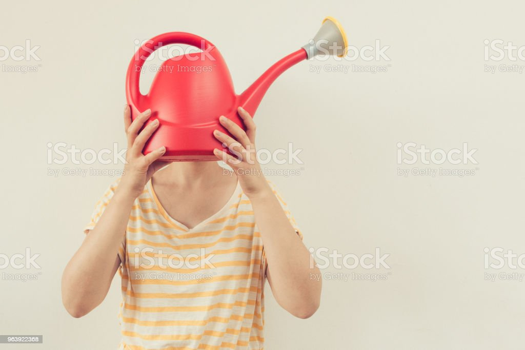 Funny portrait girl holding watering can in front of her face as a symbol for successful gardening - Royalty-free Adult Stock Photo