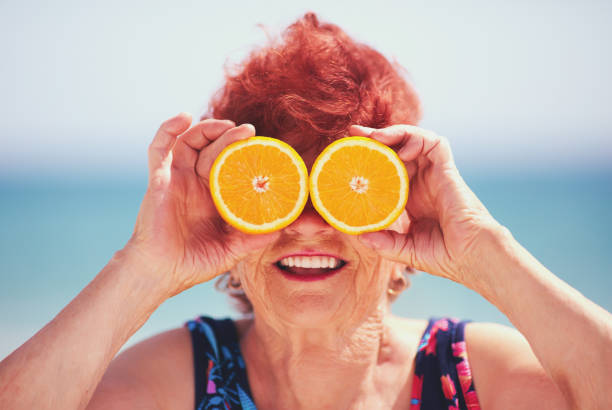 funny portrait of happy mature woman, grandma having fun with orange eyes on summer vacation. Active lifestyle stock photo