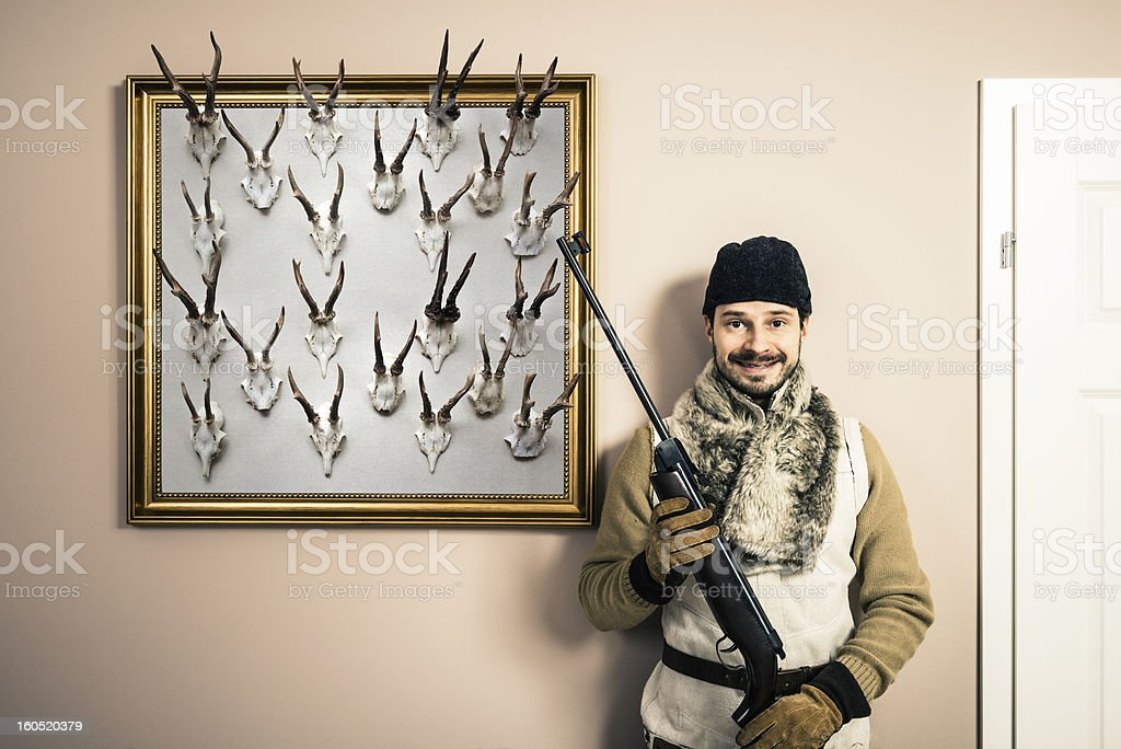 Funny portrait of hunter with shotgun and antlers, home interior royalty-free stock photo