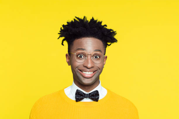 Funny portrait of nerdy young man smiling at camera Funny portrait of happy nerdy young afro American man wearing yellow sweater and black bow tie staring at camera. cheesy grin stock pictures, royalty-free photos & images