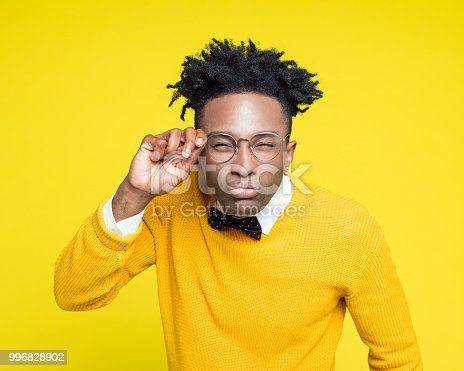 Portrait of nerdy young afro American man wearing yellow sweater and black bow tie staring at camera. Studio shot against yellow background.