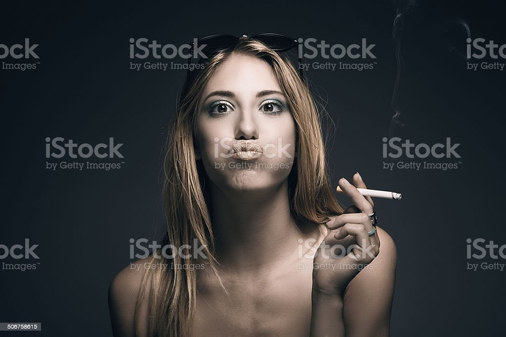 Funny portrait of young sexy woman while smoking a cigarette stock photo