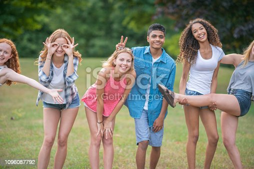 A group of teens are outdoors on a summer day. They are making funny poses.