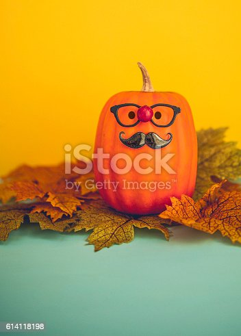 598064660istockphoto Funny pumpkin character wearing mustache and red nose for Halloween 614118198
