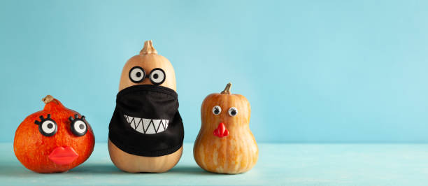 calabazas divertidas con rostros y en una máscara protectora negra sobre fondo azul pastel. - halloween covid fotografías e imágenes de stock