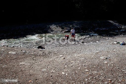 Lofer, Austria - August 11, 2019: teenage son watches while his father puts his head into freezing mountain river water to cool himself off after a hike in Austrian Alps